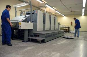 Funcionários trabalham próximos a uma grande impressora industrial